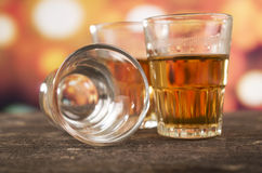 Glass of rum whiskey over defocused lights Royalty Free Stock Images