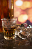 Glass of rum whiskey over defocused lights Stock Images