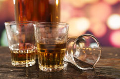 Glass of rum whiskey over defocused lights Royalty Free Stock Photos