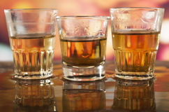 Glass of rum whiskey over defocused lights Royalty Free Stock Photography