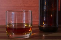 Glass with rum on wood background stock images