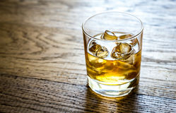 Glass of rum on the wooden background Royalty Free Stock Image
