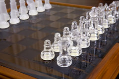Glass and sandblasted chess pieces on glass chessb. Oard with wooden frame Stock Photos