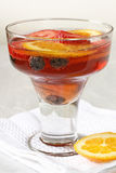 Glass of Sangria. Glass of red wine sangria with fruit on white bar napkin stock images