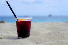 Glass of sangria on the beach. Plastic glass of sangria in the beach with sea at background stock photos