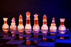 Glass schack på en schackbräde tände vid blått och orange ljus royaltyfri bild