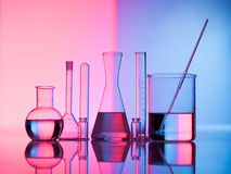 Glass science. Different laboratory glassware with water and empty with reflection. Pink and blue tint background Stock Photo
