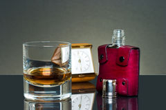 Glass of scotch and flask. Near a clock Stock Photos