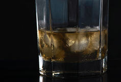 Glass of Scotch III. Glass of scotch in low key light, black background Royalty Free Stock Photos