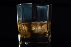 Glass of Scotch IV. Glass of scotch in low key light, black background Royalty Free Stock Photo