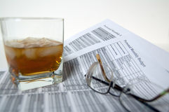 A glass of scotch, on the rocks, sits atop a personal monthly budget statement Stock Photo