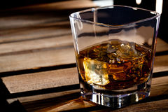 Glass of scotch whiskey. And ice on a wooden table Royalty Free Stock Photo
