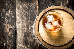 Glass of Scotch whiskey with a barrel. On a wooden background Stock Photo