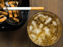 Glass of Scotch Whiskey and a Cigarette in an Ashtray Stock Photo
