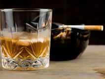 Glass of Scotch Whiskey and a Cigarette in an Ashtray Stock Photography