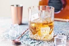 Glass of scotch whiskey. With ice cubes, bottle and copper bar accessories stock images