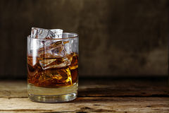 Glass of scotch whiskey with ice cubes on a rustic wooden table Royalty Free Stock Photos