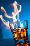 Glass of scotch whiskey and ice with fire on blue Stock Image