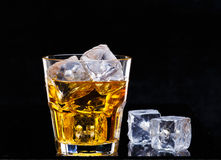 Glass of scotch whiskey and ice. Over black background Royalty Free Stock Photos