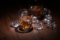 Glass of scotch whiskey and ice. On wooden table on brown background Royalty Free Stock Photography