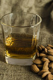 Glass of scotch whiskey on wool sack with almond seeds Stock Photography