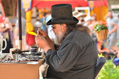 Glass Sculpture Craftsman. A craftsperson in a tophat sits at a small bench in front of a torch, fashioning a small glass sculpture Royalty Free Stock Images