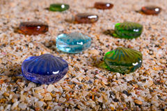 Glass sea shells with sand as background Stock Photos