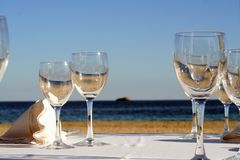 A glass of Sea and Sun. Dinner/lunch table on the beach Royalty Free Stock Image