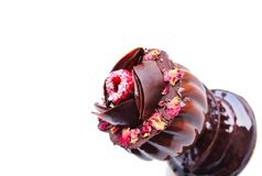 Glass shaped dessert with dried rose petals and raspberry on white background stock photo