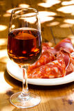 Glass of sherry with a snack on wooden table Royalty Free Stock Image