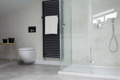 Glass shower in bright bathroom. Interior with toilet and white towel on black heater Royalty Free Stock Photography
