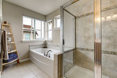 Glass shower and white bathtub in clean bathroom interior. Glass shower and white bathtub in clean bathroom interior with mosaic tile trim. Northwest, USA Stock Image