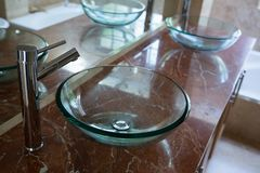 Glass sinks with steel taps installed on marble platform. In bathroom Royalty Free Stock Photos