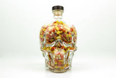 Glass skull filled with candy corn isolated. Halloween candy corn filling a glass skull Royalty Free Stock Images