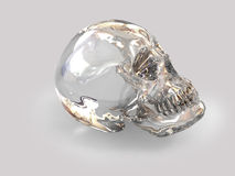 Glass skull. The skull of the person is made of a crystal of transparent white quartz, on a grey background Royalty Free Stock Photos