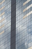 Glass skyscraper with blue sky and clouds reflected in windows. Royalty Free Stock Photo