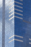 Glass skyscraper with blue sky and clouds reflected in windows. Royalty Free Stock Photos