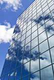 Glass Skyscraper Building. Glass skyscraper front with a reflection of the sky and clouds Royalty Free Stock Photography