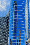 Glass skyscraper. Curved oval glass skyscraper in downtown houston with reflections of other buildings Royalty Free Stock Photography