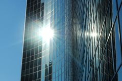 A glass skyscraper with the sun glistening Royalty Free Stock Photo