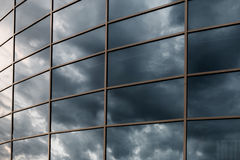 Glass skyscraper wall with reflection of dark stormy clouds at s Stock Photos