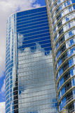 Glass skyscrapers. Curved oval glass skyscraper in downtown houston with reflections of other buildings Royalty Free Stock Photos
