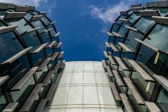 Glass skyscrapers of irregular shape. Bottom view. Abstract architectural detail of corporate building suitable as background. Abstract architectural detail of royalty free stock images