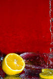 Glass with a slice of a lemon. In drops of water on a red background Royalty Free Stock Photo