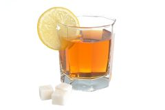 Glass with a slice of lemon filled with lemon tea and refined su Royalty Free Stock Photos