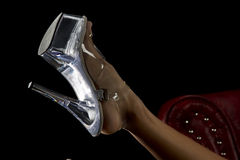 Glass slipper. A womans leg up in the air with a clear shoe on her foot capturing the sparkle from the light Stock Photography