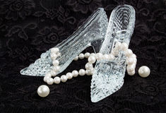 Glass slippers with pearls on a black lace Stock Photo