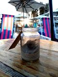 Glass small container with beach sand. In the background a beautiful sunset stock photos