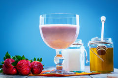 Glass of smoothie with fresh strawberries, honey and yogurt Stock Images