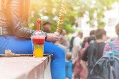 A glass of smoothie made from fresh fruit with strawberry stands on the parapet on the background of blurred street on a Sunny day Royalty Free Stock Images